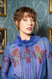 Milla Jovovich worked a messy updo with wispy bangs at the Miu Miu Cruise show.