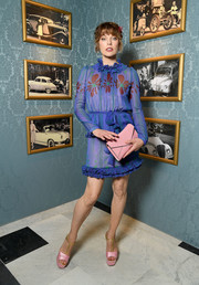 Milla Jovovich charmed in a blue floral dress with a ruffle neckline and hem at the Miu Miu Cruise show.