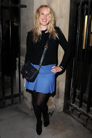 Ludivine paired her pleated skirt and black cardigan with a navy shoulder bag.