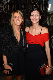 Giovanna Battaglia paired a red off-the-shoulder blouse with a high-waist skirt for a chic finish at the Miu Miu fashion show.