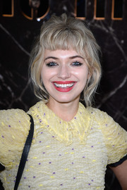 Imogen Poots oozed a youthful, grungy vibe with her messy updo and baby bangs at the Miu Miu fashion show.