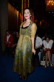 Ulyana Sergeenko looked lovely at the Miu Miu fashion show in a yellow sheer-overlay dress with a subtle flower print.
