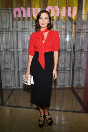 For her bag, Maggie Gyllenhaal chose a chic embellished leather clutch by Miu Miu.