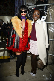 Lupita Nyong'o finished off her cropped jacket-mini skirt combo with a classy white wool coat for the Miu Miu fashion show.