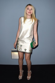 Dakota Fanning completed her retro getup with a pair of bejeweled nude platform sandals by Miu Miu.