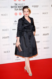 Olivia Colman completed her metallic-themed accessories with a studded gold clutch.