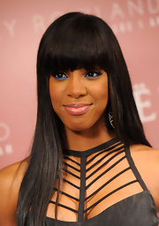 Pop star Kelly Rowland wore a strappy black dress for the launch of her new album, 'Here I Am.' For a pop of color, she opted for bright blue eyeliner to finish off the look.
