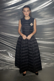 Millie Bobby Brown look hip in a black puffer maxi dress at the Moncler Genius show.
