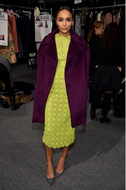 Ashley Madekwe mixed colors so stylishly at the Monique Lhuillier fashion show, pairing a plum wool coat with a neon-yellow lace dress.