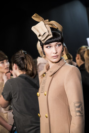 Bella Hadid looked cool wearing this cardboard-and-packing tape hat at the Moschino runway show.