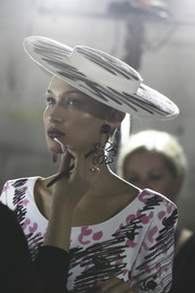 Bella Hadid looked theatrical wearing this wide-brimmed scribble-print hat at the Moschino Spring 2019 show.