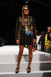 Anna dello Russo rocked a shift dress studded all over with huge gold buttons during the Moschino fashion show.