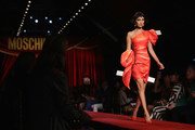 Bella Hadid shimmied down the Moschino runway wearing a frilly orange one-shoulder dress.