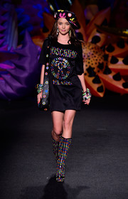 Miranda Kerr looked cool on the Moschino runway in a black T-shirt dress adorned with multicolored rings.