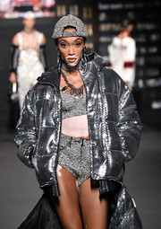 Winnie Harlow walked the Moschino x H&M runway rocking a pair of bedazzled hot pants and a matching bustier and baseball cap.
