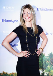 Jennifer Aniston offset her black dress with a layered gold neckalce.