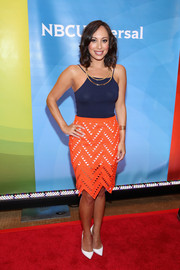 Cheryl Burke's orange geometric-cutout pencil skirt made a chic color contrast to her top.