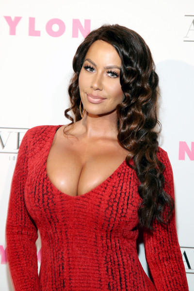 Amber Rose covered up her buzz cut with a curly brown wig when she attended the Nylon Young Hollywood Party.