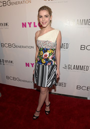 Kiernan Shipka teamed her vibrant dress with strappy black mules by Jimmy Choo.