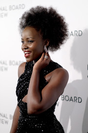 Lupita Nyong'o teamed her earrings with some stackable diamond rings.