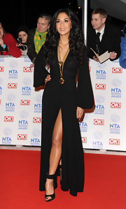 Nicole showed some leg in this elegant bell-sleeved black gown with a thigh-high slit.