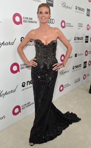Heidi Klum stuck a pose in this  body-hugging black strapless gown with a long train.