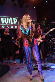 Kat Graham went psychedelic in a multicolored striped pantsuit for her performance during the new BUILD Studio opening.