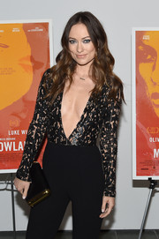 Olivia Wilde attended the New York screening of 'Meadowland' carrying a black and gold Michael Kors clutch.