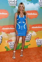 Heidi Klum paired her sassy dress with white ankle-cuff sandals.
