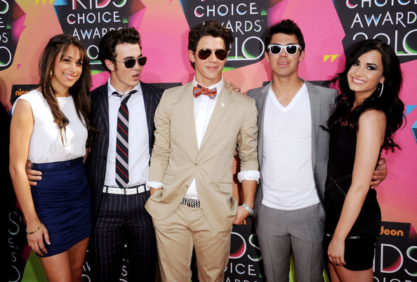 Nick wore a tan suit with classic gold aviator sunglasses.