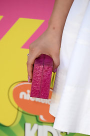 Lucy Hale added a pop of color to her white dress with this fuchsia, hard-case clutch.
