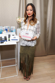 Jamie Chung teamed her blouse with a fringed green suede skirt for an even chicer look.