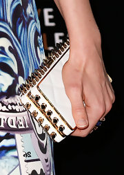 Bella Heathcote carried a sleek white clutch with gold spike details on the edges at the Rodeo Drive Walk of Style.