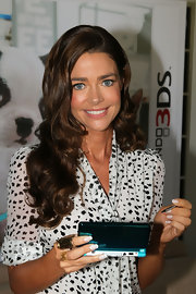 Denise Richards donned long curls at a Nintendo event. The actress provided a frame for her face with a subtle side part.