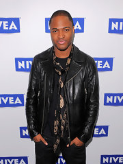Taio wears a sleek leather jacket with zipper accents.
