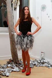 Olivia Ruiz paired her feathered sequin cocktail dress with vibrant red pumps.