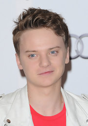 Conor's short wavy hair is his signature look.