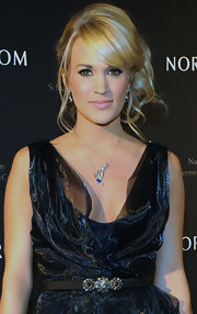 Carrie Underwood attended the Nordstrom Symphony fashion show wearing her hair in a side looped ponytail with soft loose curls and side-swept bangs.