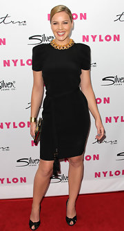 Abbie dons a little black dress with strong shoulders and a dramatic rope belt for the Nylon Anniversary party.