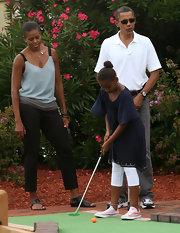 Sasha Obama was looking stylish as she played mini golf in a navy peasant blouse and white leggings.