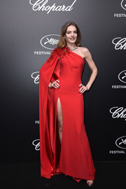 Natalia Vodianova looked downright divine in a red cape-sleeve one-shoulder gown by Atelier Versace at the Trophee Chopard dinner.