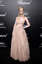 Elle Fanning charmed at the Trophee Chopard dinner in a strapless nude Prada gown that was adorned with droopy flowers.