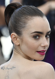 Lily Collins looked ultra modern wearing this tight updo that was a cross between a bun and a segmented ponytail during the Cannes Film Fest photocall for 'Okja.'