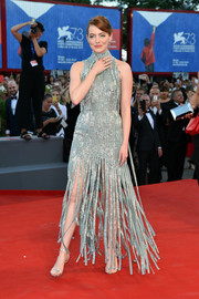 Emma Stone was a vision in a high-neck silver Atelier Versace gown, rendered in intricately beaded strips of fabric, during the Venice Film Festival opening ceremony.