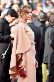 Clotilde Courau paired a maroon leather clutch with a caped beige dress for the Cannes Film Festival premiere of 'La Tete Haute.'
