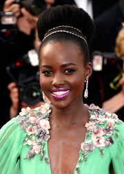 Never shy with colors, Lupita Nyong'o paired a bright purple lip with her jade-green gown.