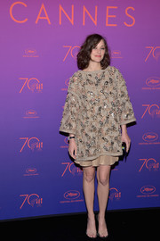 Marion Cotillard donned a beige Chanel ensemble, consisting of a loose, beaded top and a matching mini skirt, for the Cannes Film Festival opening gala dinner.