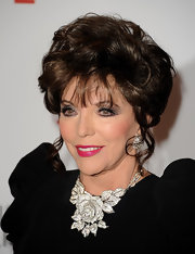 Joan Collins smiled for the camera at the opening gala of The Resnick Pavilion wearing a chic bobby-pinned updo.