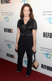 Kristin Davis accessorized her outfit with a nude and black wristlet.