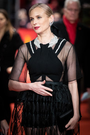 Diane Kruger paired a black satin clutch with a partially sheer dress for the Berlinale premiere of 'The Operative.'